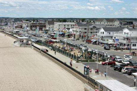 The boardwalk at Hampton Beach, N.H., is flanked by hotels and honky-tonk, parking spaces and playground spires.